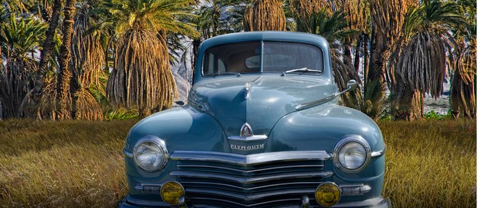 Vintage Blue Plymouth Automobile against Palm Trees and Cloudy Blue Sky near Palm Springs California Coffee Mug