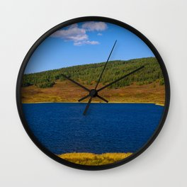 Calm water pond with greenery on mountain in background Wall Clock