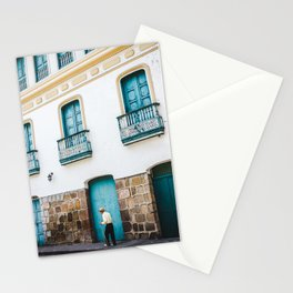 Old Colombian man with walking stick making his way past colourful turquoise & white house in Santander Colombia Stationery Cards