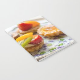 Small fruit tarts laid out on an antique china plate Notebook