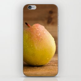 One fresh pear with water drops on rustic wood against a rustic wooden background close front view iPhone Skin