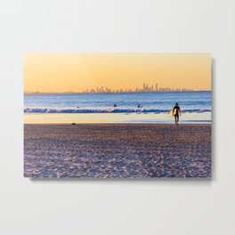 Surfer walks away from the sea on Coolangatta beach at sunset. Surfer's Paradise is in the backgroun Metal Print