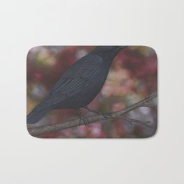 crow on a branch bokeh Bath Mat