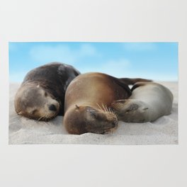 Sea lions family sleeping together on beach Rug