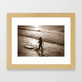 Little surfer girl runs in the waves with her bodyboard Framed Art Print