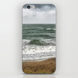 Land and sea under stormy clouds iPhone Skin