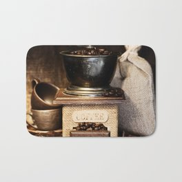 Still life with Antique coffee grinder, burlap sack, coffee cups and chocolate on  rustic table Bath Mat