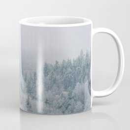 Foggy mountains are covered with bright white trees and dark evergreens Coffee Mug