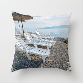 Pebble beach, chaise-longues and umbrellas in Istria, Croatian coast Throw Pillow