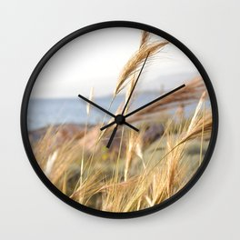 Wild grass in the wind by the sea Wall Clock