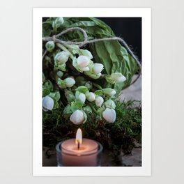 Christmas Roses with one burning tea candle macro front view with dark background Art Print