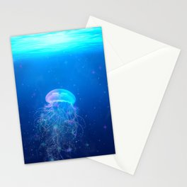Glowing and sparkling blue jellyfish swimming in mystical deep blue ocean Stationery Cards