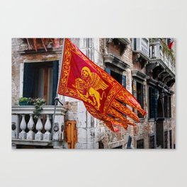 Colors of Venezia, golden-red flag, old building at background Canvas Print