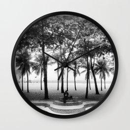 black man sitting in the shade of coconut trees on copacabana beach Wall Clock