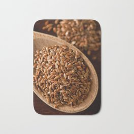 Brown flax seeds portion on wooden spoon Bath Mat