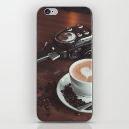 A cup of hot cappuccino placed on a table next to the old camera with lens and coffee beans iPhone Skin