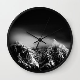 Black and white long exposure of clouds above mountain Wall Clock