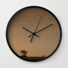 Lone wildebeest grazing in South Africa at sunset Wall Clock