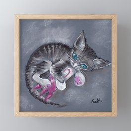 A kitten with blue eyes playing with a toy rocket Framed Mini Art Print