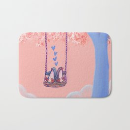 Penguins in Love on Their Tree Swing in a Pink Sky Bath Mat