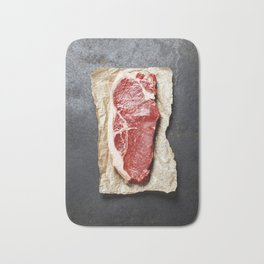 Raw beef steak on a dark slate background Bath Mat