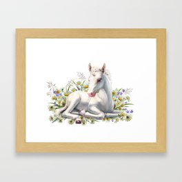 Baby unicorn lies in flowers Framed Art Print
