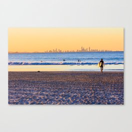Surfer walks away from the sea on Coolangatta beach at sunset. Surfer's Paradise is in the backgroun Canvas Print