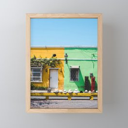 White fedora hats lined up for sale outside colorful yellow and green houses in Cartagena, Colombia Framed Mini Art Print