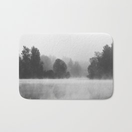 Trees disappearing in morning fog above the lake Bath Mat