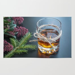 Whisky in glass with natural jute hemp cord ribbon bow on dark background Rug