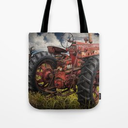 Abandoned Old Farmall Tractor in a Grassy Field on a Farm Tote Bag