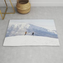 People having fun and running in mountains on the background of high snow-capped peaks Rug