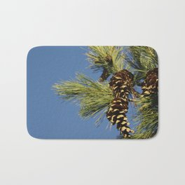 Pine cones and branches against a blue autumn sky Bath Mat