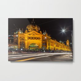 Flinders street station at night with light trails of cars passing by Metal Print