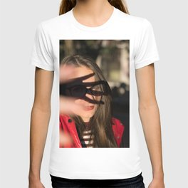 Portrait of young girl covering her face to block sun light T-shirt