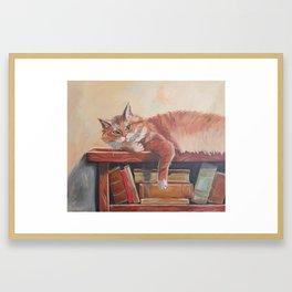 Red cat on a bookshelf Framed Art Print