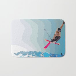 Man jumps with skies on piste with mountains and sky background Bath Mat