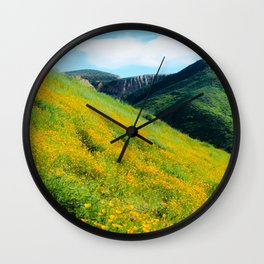 yellow poppy flower field with green leaf and green mountain and cloudy blue sky in summer Wall Clock