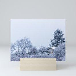 Snowy winter cabin in the woods Mini Art Print