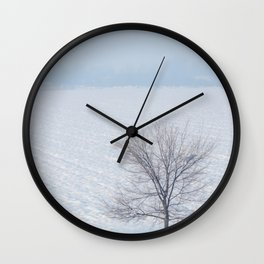 Lonely tree standing on a field with snow Winter landscape. Wall Clock