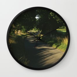 Evening light on a small country road lined with Oak trees. Norfolk, UK. Wall Clock