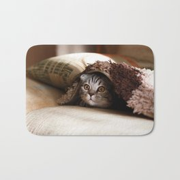 Cute kitten looking from sofa Bath Mat