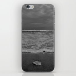 A lonely sea shell in the surf of Assateague Island (black and white) iPhone Skin