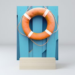 Summer holidays. Orange lifeguard over a blue wooden gate Mini Art Print