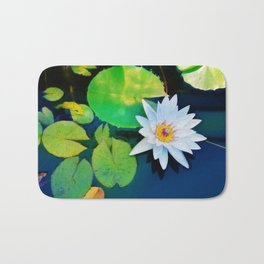 Lone water Lily afloat above the lily pads Bath Mat