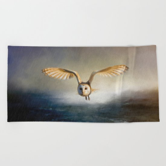An owl flies over the lake Beach Towel
