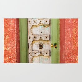 White and green wooden door with red wall in a typical village in Provence France Rug