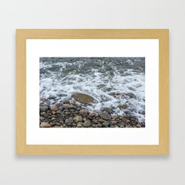Wave washing over pebbles Framed Art Print