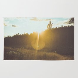 sunset slanted in a field Rug