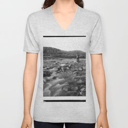 Man with rifle stands in mountain stream as it floods, east of Palmdale, California, ca.1920 Unisex V-Neck